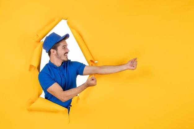 Mensajero masculino de vista frontal en uniforme azul en el espacio amarillo