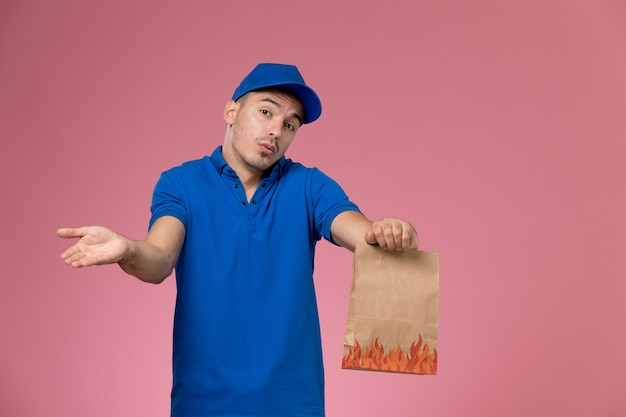 Mensajero masculino de vista frontal en uniforme azul con paquete de alimentos de papel en la pared rosa, entrega de servicio uniforme de trabajador de trabajo