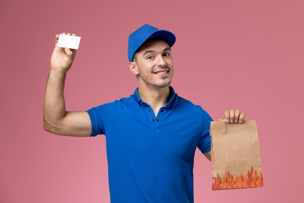 Mensajero masculino de vista frontal en uniforme azul con paquete de alimentos de papel con tarjeta en la pared rosa, entrega de servicio uniforme de trabajador
