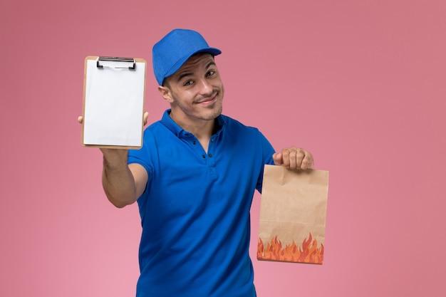 Mensajero masculino de vista frontal en uniforme azul con paquete de papel de alimentos y bloc de notas en la pared rosa, entrega de trabajo de servicio uniforme