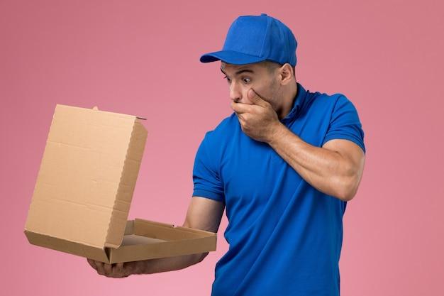 Mensajero masculino de vista frontal en uniforme azul sosteniendo la apertura de la caja de entrega de alimentos con expresión de sorpresa en la pared rosa, entrega de trabajo de servicio uniforme