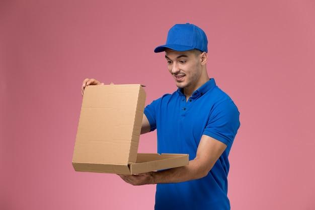 Mensajero masculino de vista frontal en uniforme azul sosteniendo la apertura de la caja de entrega de alimentos en la pared rosa, entrega de trabajo de servicio uniforme