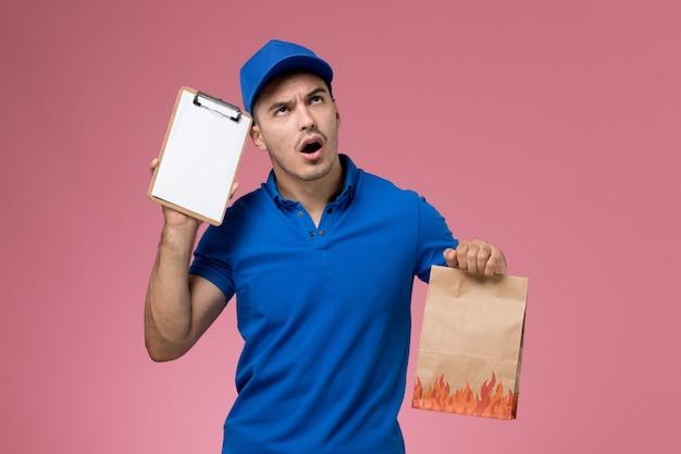 Mensajero masculino de vista frontal en uniforme azul sosteniendo el paquete de papel de bloc de notas en la pared rosa, entrega de servicio uniforme del trabajador
