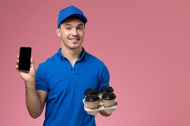 Mensajero masculino de vista frontal en uniforme azul sosteniendo sus tazas de café de teléfono en la pared rosa, entrega de servicio uniforme de trabajador