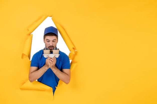 Mensajero masculino de vista frontal en uniforme azul sosteniendo tazas de café en el espacio amarillo