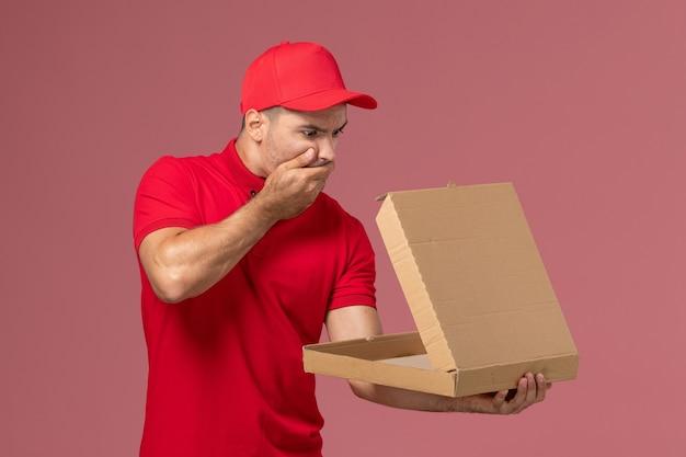 Mensajero masculino de vista frontal en uniforme rojo y capa con caja de comida con expresión de sorpresa en trabajador de pared rosa claro