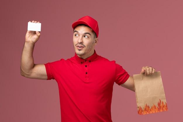 Mensajero masculino de vista frontal en uniforme rojo y capa con paquete de alimentos y tarjeta en el uniforme de trabajo de trabajador de entrega de servicio de escritorio rosa