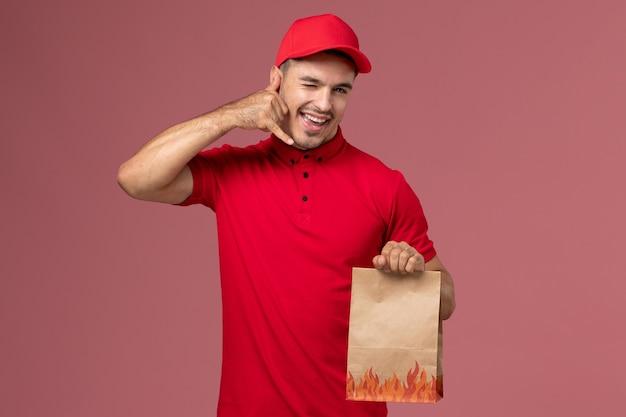 Mensajero masculino de vista frontal en uniforme rojo y capa con paquete de comida de papel guiñando un ojo en el trabajador de la pared rosa