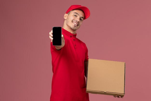 Mensajero masculino de vista frontal en uniforme rojo y capa sosteniendo la caja de comida junto con el teléfono sonriendo en el trabajo de servicio de pared rosa uniforme de reparto masculino