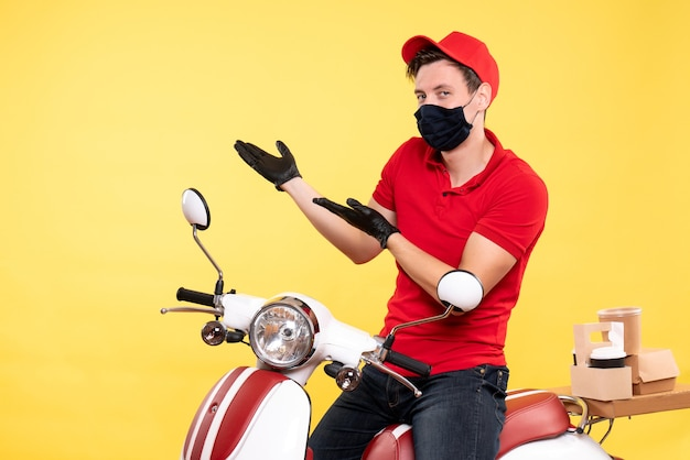 Mensajero masculino de vista frontal en uniforme rojo y máscara en amarillo