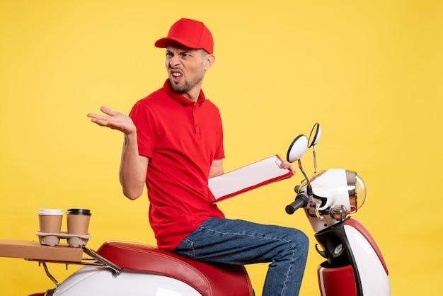 Mensajero masculino de vista frontal en uniforme rojo con nota de archivo en el trabajo de servicio de trabajador uniforme de entrega de color amarillo bicicleta