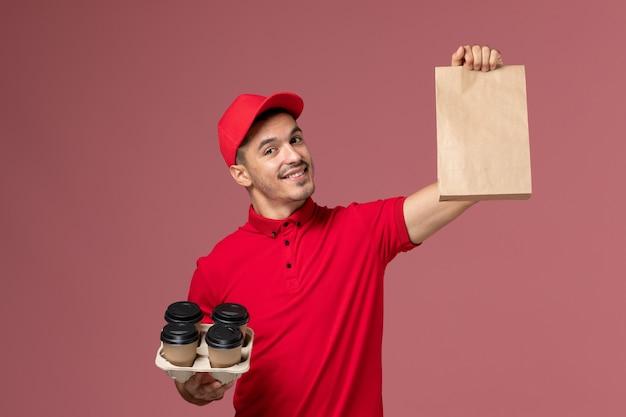 Mensajero masculino de vista frontal en uniforme rojo sosteniendo tazas de café de entrega marrón con paquete de comida en uniforme de trabajador de trabajo de entrega de servicio de escritorio rosa