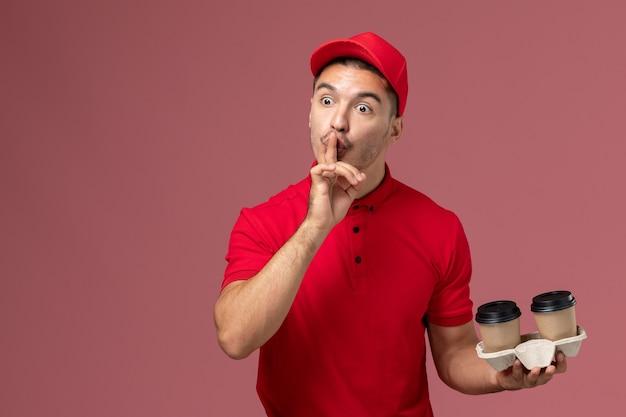 Mensajero masculino de vista frontal en uniforme rojo sosteniendo tazas de café de entrega marrón en la pared rosa trabajador masculino