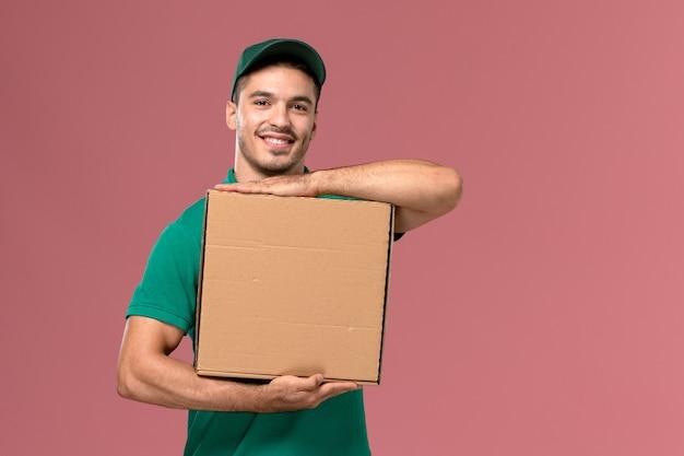 Mensajero masculino de vista frontal en uniforme verde con caja de comida con una sonrisa en el fondo de color rosa