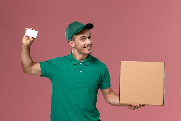 Mensajero masculino de vista frontal en uniforme verde con caja de comida con tarjeta blanca en escritorio rosa