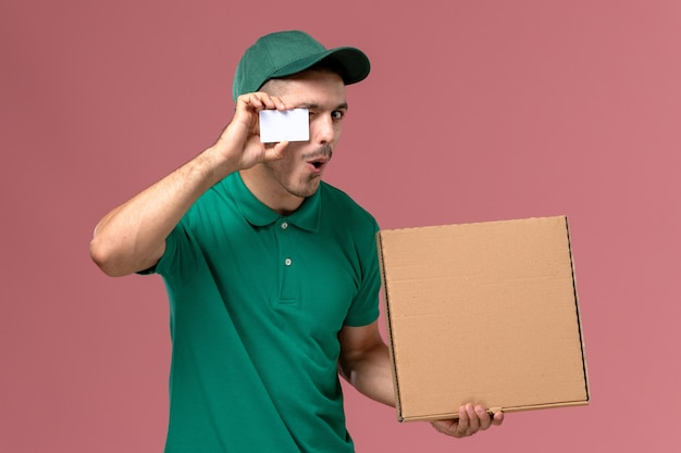 Mensajero masculino de vista frontal en uniforme verde con caja de comida con tarjeta blanca sobre fondo rosa