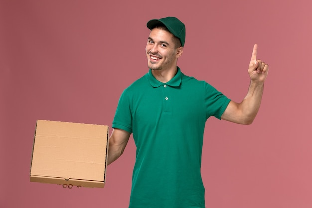 Mensajero masculino de vista frontal en uniforme verde con caja de entrega de alimentos con el dedo levantado sobre fondo rosa
