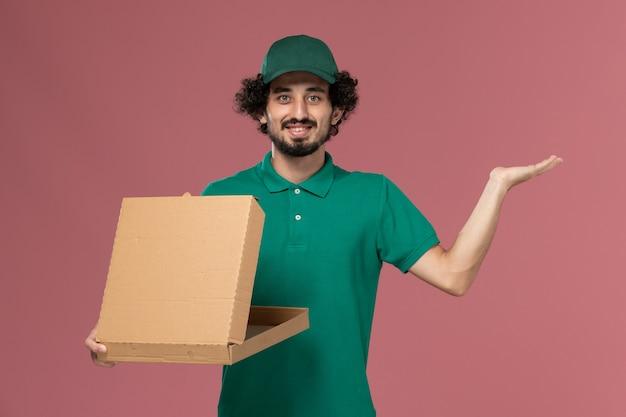 Mensajero masculino de vista frontal en uniforme verde y capa sosteniendo y abriendo la caja de comida de entrega sobre fondo rosa servicio de entrega uniforme del trabajador