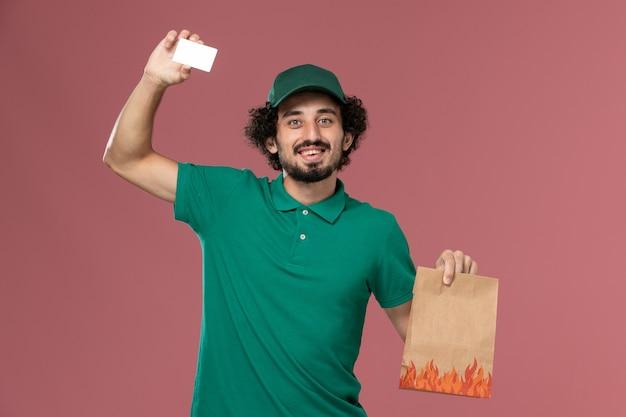 Mensajero masculino de vista frontal en uniforme verde y capa sosteniendo la tarjeta y el paquete de alimentos en el servicio de fondo rosa uniforme trabajador de trabajo masculino