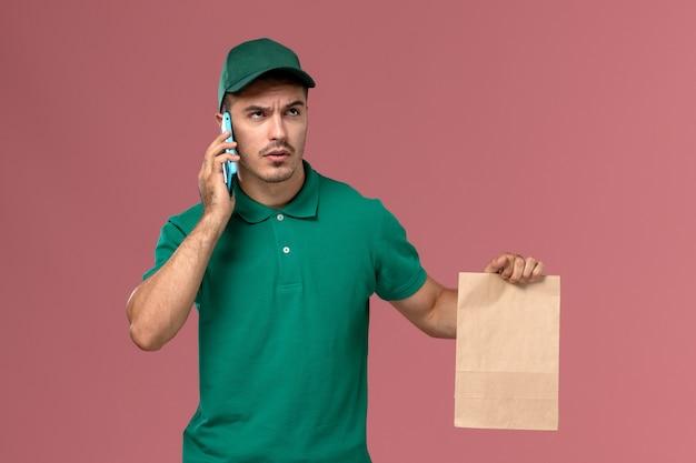 Mensajero masculino de vista frontal en uniforme verde sosteniendo el paquete de alimentos mientras habla por teléfono sobre fondo rosa