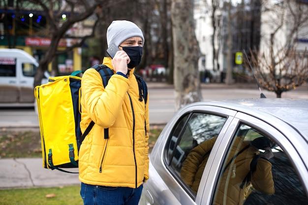 Mensajero con mochila amarilla y máscara médica negra cerca de un automóvil hablando por teléfono