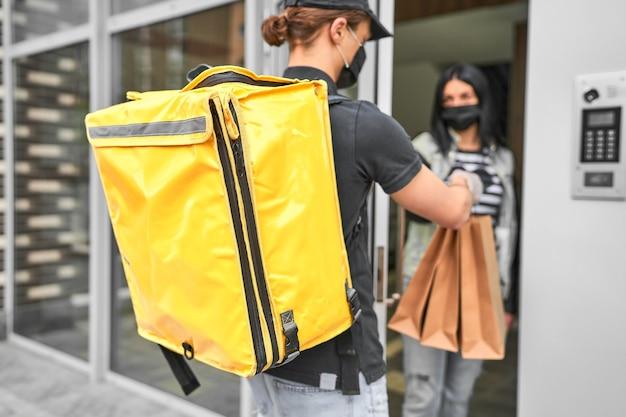 Un mensajero con mochila y comida entregó un pedido en línea a la casa del cliente.