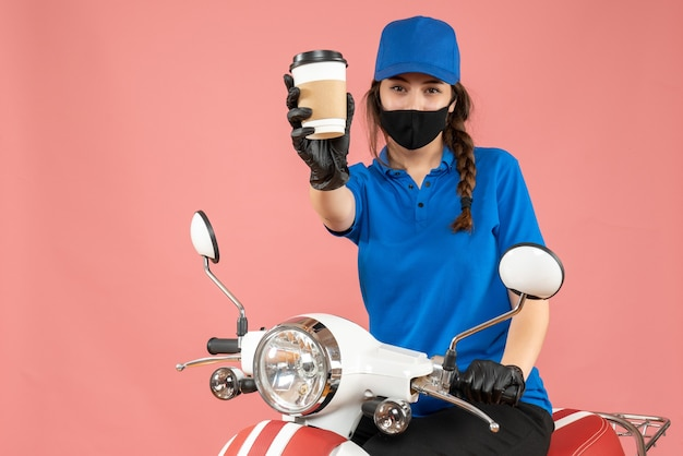 Mensajero mujer confiada con máscara médica negra y guantes entregando pedidos sobre fondo melocotón