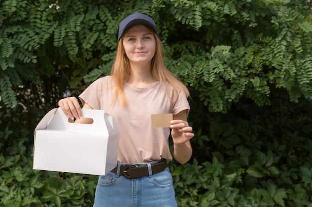 Mensajero mujer con gorra azul con postre en caja de cartón sin marcar y una tarjeta de visita una maqueta para la presentación. concepto de servicio de entrega. área de publicidad.