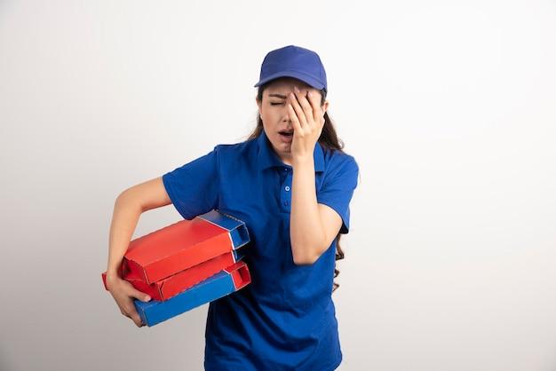 Mensajero mujer joven con cartón de pizza y portapapeles