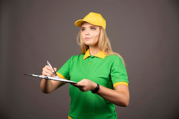 Mensajero mujer joven con lápiz y portapapeles mirando a otro lado. foto de alta calidad