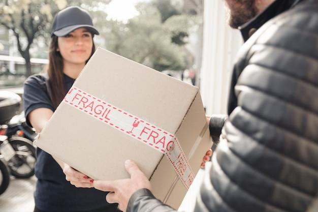 Mensajero mujer joven que entrega el paquete al hombre