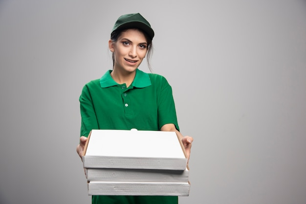 Mensajero mujer joven regalando cajas de pizza sobre fondo gris.