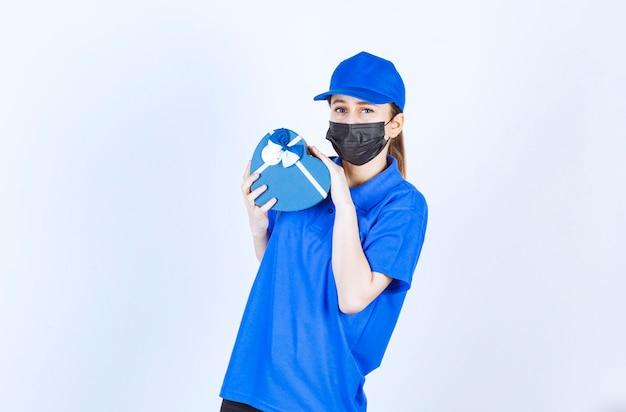 Mensajero mujer con máscara y uniforme azul sosteniendo una caja de regalo con forma de corazón.