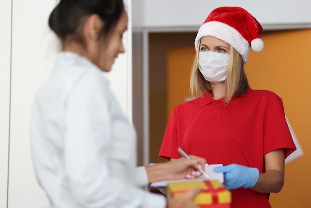 Mensajero mujer con sombrero rojo de santa claus y máscara médica protectora en la cara le da al cliente para firmar el documento y el regalo