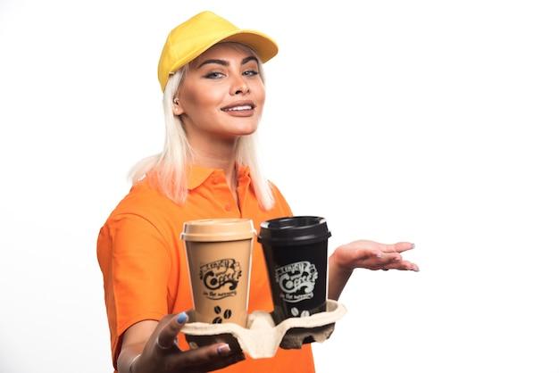 Mensajero mujer sosteniendo dos tazas de café sobre fondo blanco mientras sonríe. foto de alta calidad