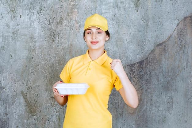 Mensajero mujer en uniforme amarillo entregando una caja de comida para llevar blanca y mostrando los músculos de su brazo.