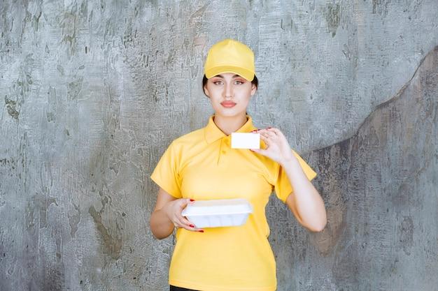 Mensajero mujer en uniforme amarillo entregando una caja de comida para llevar blanca y presentando su tarjeta de visita.