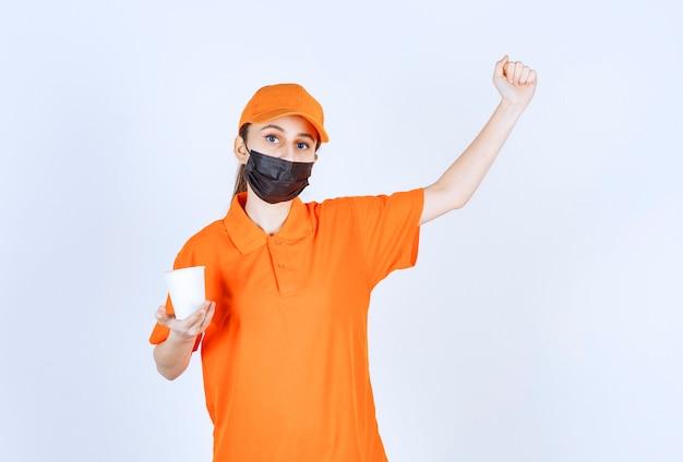 Mensajero mujer en uniforme amarillo y máscara negra sosteniendo una bebida para llevar y mostrando su puño.