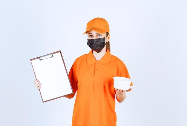Mensajero mujer en uniforme amarillo y máscara negra sosteniendo un vaso de plástico y lista de clientes.