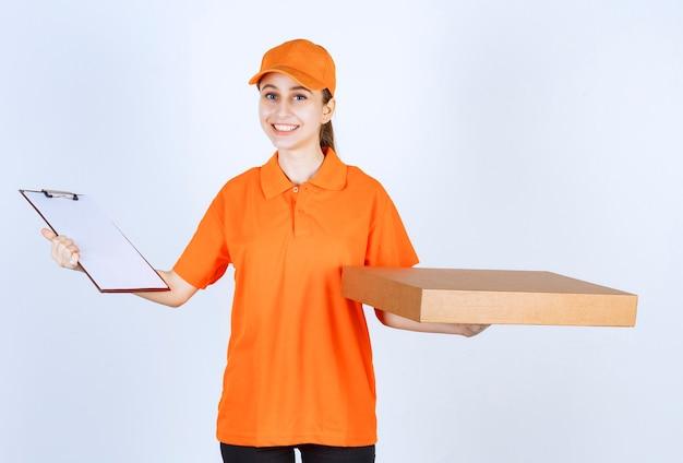 Mensajero mujer en uniforme naranja sosteniendo una caja de pizza para llevar y una libreta de direcciones.