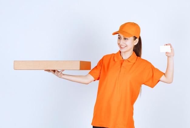 Mensajero mujer en uniforme naranja sosteniendo una caja de pizza para llevar y presentando su tarjeta de visita.