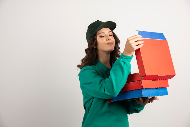 Mensajero mujer en uniforme verde oliendo la pizza caliente.