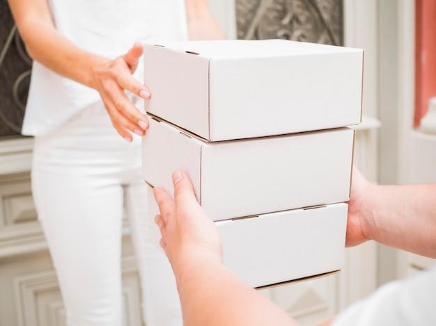 Mensajero de primer plano entregando cajas