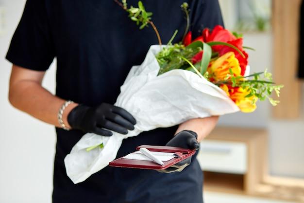 Mensajero, repartidor en guantes médicos de látex entrega de forma segura compras en línea un ramo de flores