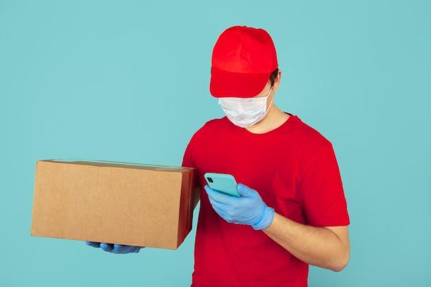 Mensajero con ropa roja sosteniendo una caja grande y usando el teléfono en la caja azul.