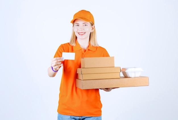 Mensajero de sexo femenino joven con una camiseta naranja que muestra la tarjeta mientras sostiene las cajas y el recipiente de plástico frente a la pared blanca