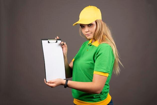 Mensajero de sexo femenino joven con el lápiz que muestra el portapapeles. foto de alta calidad