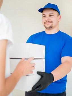 Mensajero sonriente entregando cajas