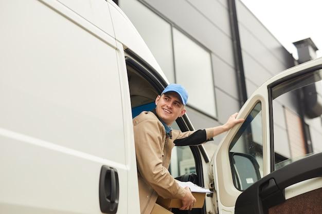 Mensajero sonriente joven que sostiene el paquete mientras está sentado en la camioneta que entrega paquetes