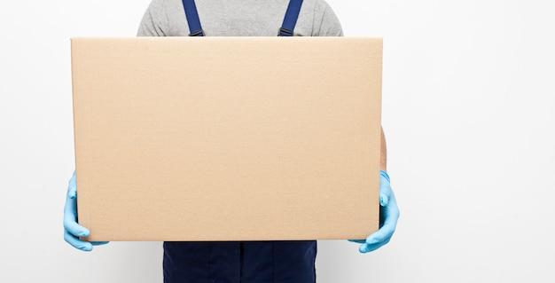 El mensajero está sosteniendo la caja de cartón en la mano con guantes de látex protectores en gris